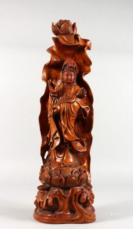 A CHINESE CARVED WOOD FIGURE OF GUANYIN on a lotus base. 20.5ins high.