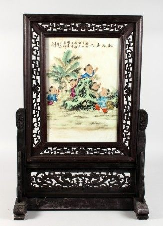 A CHINESE PORCELAIN TABLE SCREEN, in a carved hardwood frame. 26.5ins high x 18ins wide.