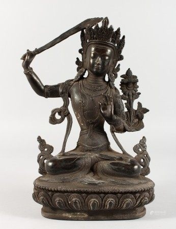 A THAI CAST METAL SEATED DEITY, holding a sword in her right hand. 12ins high.