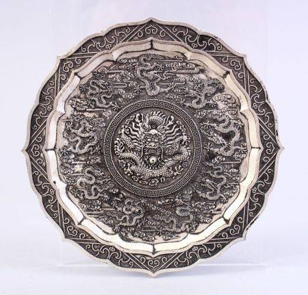 A CHINESE WHITE METAL DRAGON DISH, decorated with many dragons amongst clouds, 12cm.