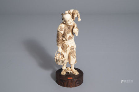 A Japanese ivory okimono of a fruit seller and his