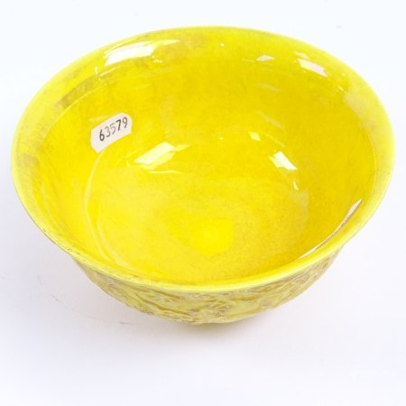 A Chinese yellow glazed bowl with embossed dragon decoration, and 6 character mark, 15.5cm diameter
