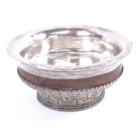 A Tibetan silver-clad and hardwood bowl, with allover chased and embossed decoration