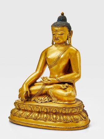 A GILT COPPER ALLOY FIGURE OF BUDDHA TIBET OR NEPAL, CIRCA 14TH CENTURY