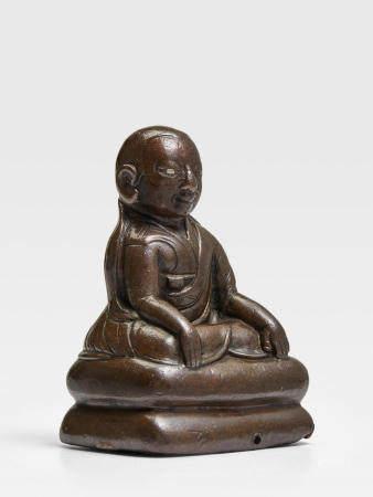 A SILVER INLAID COPPER ALLOY FIGURE OF A KAGYU LAMA TIBET, CIRCA 14TH CENTURY