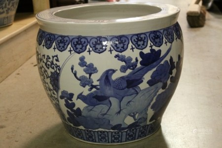 A large blue and white Chinese style fish bowl jardiniere.