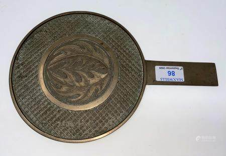 A Chinese bronze hand mirror, the back with central relief leaves against a trellis border, 4