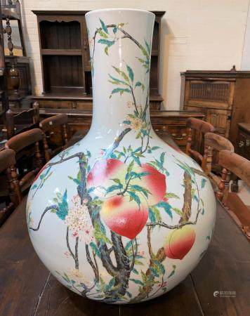 A very large Chinese porcelain bottle vase decorated in polychrome with peaches on branches, with