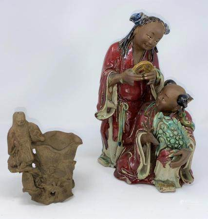 A Chinese group of figures holding a large frog with glazed decoration and a stoneware figure of a