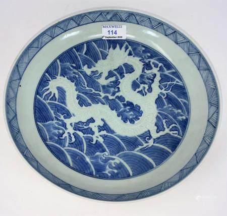 A Chinese blue and white dish decorated with central dragon, faded character mark to base with