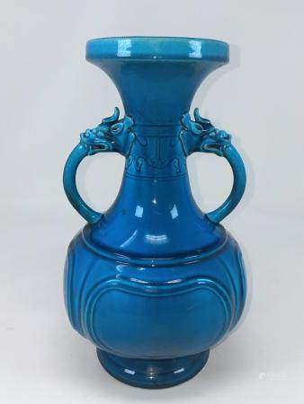 A Chinese turquoise glazed vase with double handles opening from the mouths of mythological