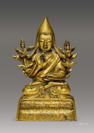 A GILT COPPER ALLOY FIGURE OF A GELUKPA LAMA, TIBETO-CHINESE, 18TH CENTURY