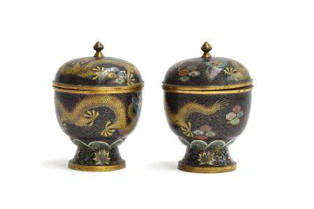 A pair of early 20th century Chinese lidded cloisonné urns, depicting dragons on a black ground