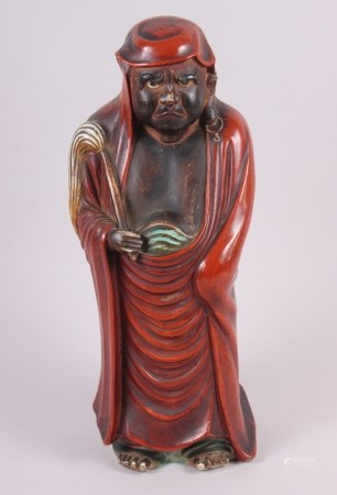 """A Chinese porcelain figure of Daruma with a fly whisk, 15"""" high"""