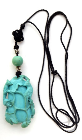Small velvet pouch containing an Oriental Inro with birds coloured in turquoise, 5cm long