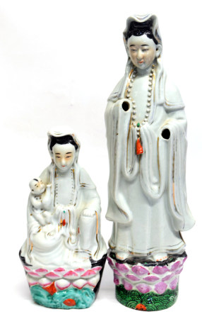 Two Chinese porcelain models of Guan Yin decorated in typical fashion, both on green bases,