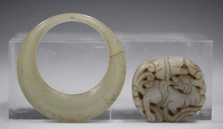 A Chinese jade oval plaque, Qing dynasty, carved and pierced with a Buddhistic lion, the stone of