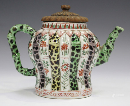 A Chinese famille verte porcelain teapot, Kangxi period, with carved wood cover, the baluster body