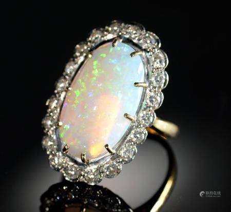 AN OPAL AND DIAMOND RING  the 10 x 19mm oval opal of fine polish, in gold marked 18ct, 7.8g, size