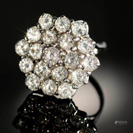 A DIAMOND CLUSTER RING  of nineteen evenly sized round brilliant cut diamonds arranged in an