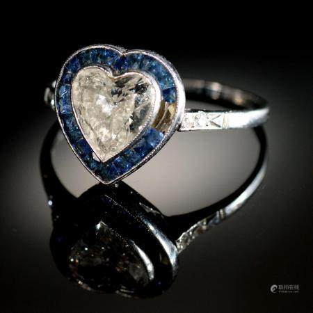 A HEART SHAPED DIAMOND AND SAPPHIRE CLUSTER RING with surround of calibre cut sapphires and
