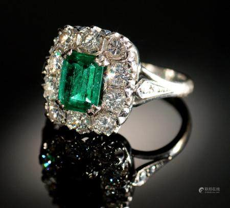 AN EMERALD AND DIAMOND RING  the step cut emerald of approx 4 x 6mm in a surround of ten evenly