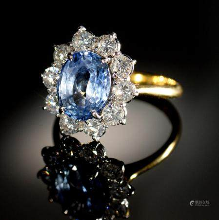 A CORNFLOWER SAPPHIRE AND DIAMOND RING  the oval sapphire in a surround of ten evenly sized round