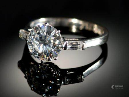 A DIAMOND RING  the round brilliant cut diamond of approx 2cts flanked by a baguette diamond to each
