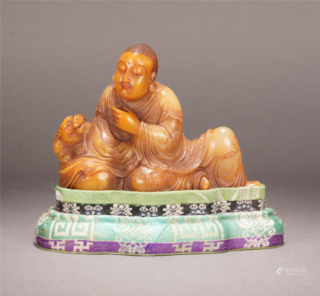 A CHINESE TIANHUANG LION AND LUOHAN SEATED STATUE