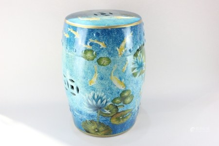 A glazed ceramic garden seat, barrel shaped, decorated with fish swimming amongst water lilies, 47cm