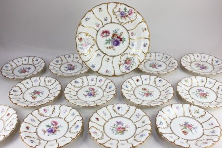 A collection of twelve Koenigszelt German porcelain plates, with floral decoration and scrolling