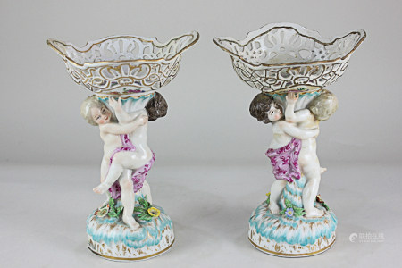 A pair of 19th century Berlin porcelain pierced pedestal dishes, the support modelled as two putti