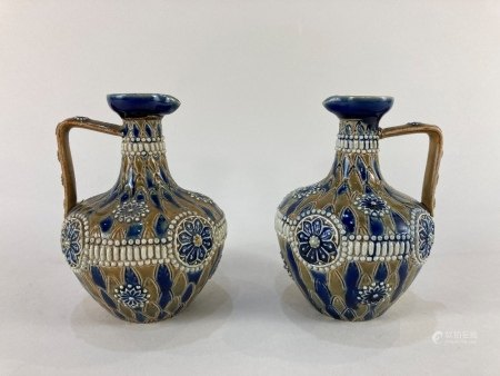 A near pair of Doulton Lambeth pottery oil jugs one by Elizabeth Atkins the other ET, with raised