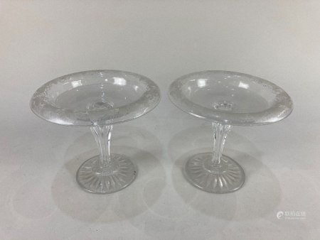 A pair of circular glass bon bon dishes with trailing vine leaf border, on baluster stems and