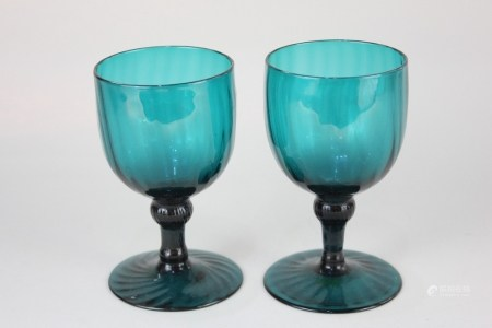 A pair of 18th century green glass goblets, with cup shaped bowls, and inverted baluster stems on