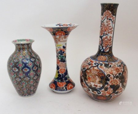 AN IMARI BOTTLE SHAPED VASE painted with figures in gardens surrounded by foliage and detailed in