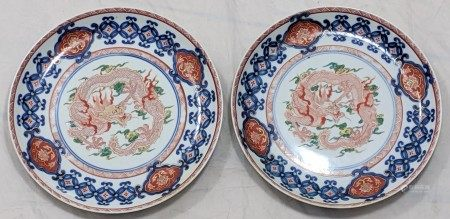 A pair of Chinese 19th century plates depicting a red five claw dragon surrounded by blue and