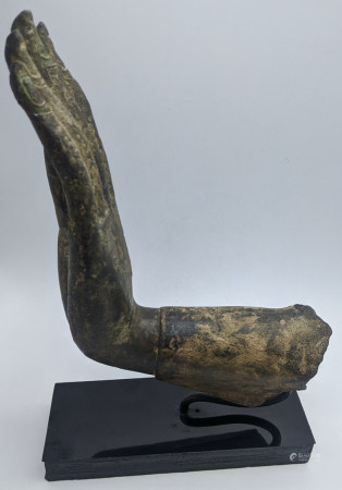 A Chiang Saen period Thai bronze hand from a Buddha image, 15th century, mounted on stand, L.16cm