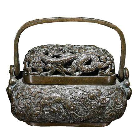 A FINELY OPENWORKED DRAGON COPPER BURNER WITH COVER