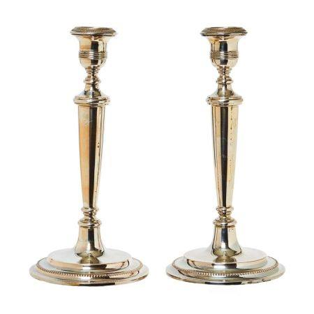 Pareja de candeleros en plata española punzonada con decoración estriada y perlada, [...]