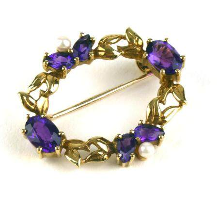 AN EARLY 20TH CENTURY 9CT GOLD, AMETHYST AND SEED PEARL BROOCH Having two pairs of pear cut