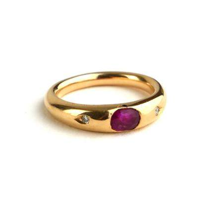 AN 18CT GOLD, RUBY AND DIAMOND RING The single oval cut ruby flanked by diamonds in a rubover