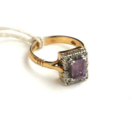 AN EDWARDIAN STYLE 9CT GOLD, AMETHYST AND DIAMOND DRESS RING The emerald cut amethyst claw set to
