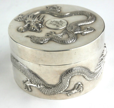 A CHINESE SILVER CIRCULAR BOX AND COVER Decorated in relief with a four toed dragon. (diameter 8cm x