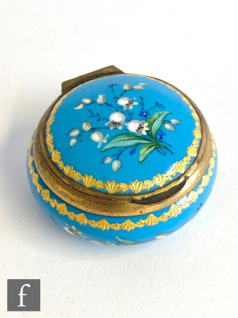 A 19th Century circular blue and gilt enamel patch box decorated with lily of the valley on a blue