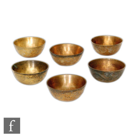 A set of six early 20th Century Chinese brass offering/rice bowls, each of rounded form, incised