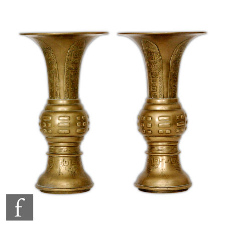 A pair of late Qing Dynasty (1644-1912) Chinese 'Eight Trigrams' (Pa Kua) brass Gu vases, the flared