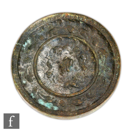 A Chinese Ming Dynasty (1368-1644) bronze mirror, the circular mirror cast with segmented borders,