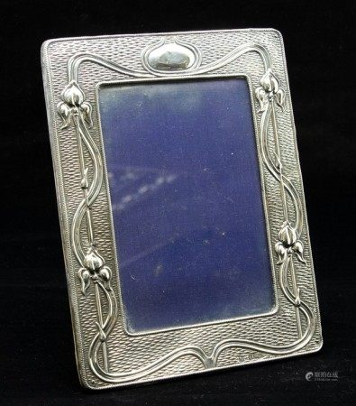 An Edwardian Art Nouveau silver photo frame, with sinuous decoration and tulip motifs on an engine