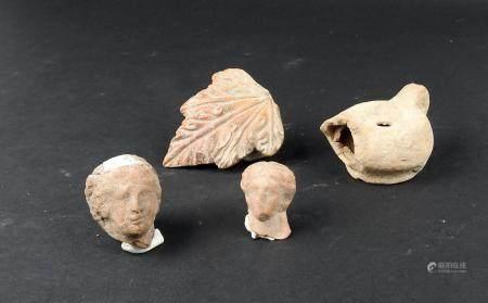 Ensemble comprenant un élément végétal, deux têtes et une lampe à huile Terre cuite Période rom